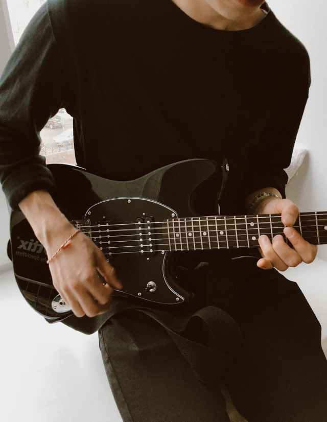 person in black long sleeve shirt playing electric guitar