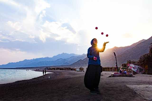 woman at the beach juggling